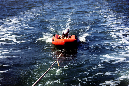 Inflatable dinghy with outboard motor at the wire swim for ship
