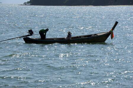 man and woman in long fishing boat with motor in ocean Banco de Imagens