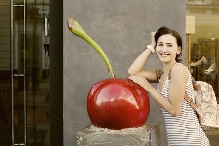 Beautiful girl with a backpack smiling and leaning on a huge artificial cherries in clothing stores