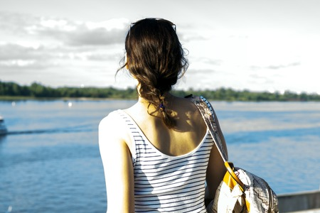 ifestyle: Young lonely girl with a backpack standing on the coast of the river hot summer