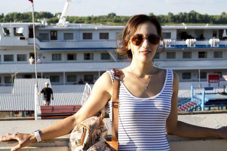 Beautiful girl with a bag on his shoulder against the background of a cruise ship