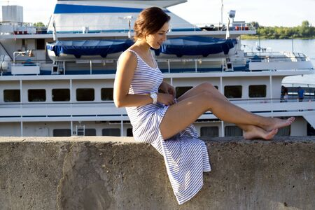 Sexy girl sits on a wharf on a background of a ship