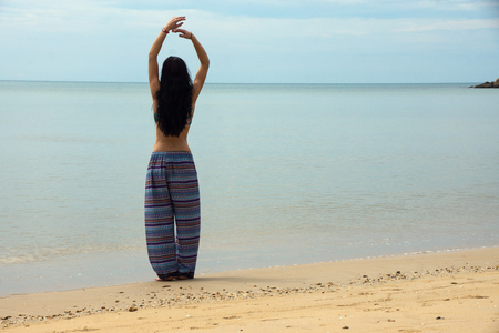 Slender girl stands on a beach with their hands stretched upwards
