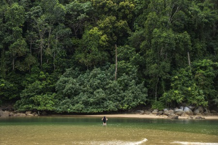 The girl stands in the water in front of the huge Hill covered with trees, Thailand