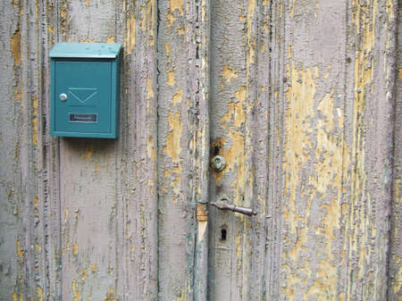 New green post box on the old ruined wooden door photo