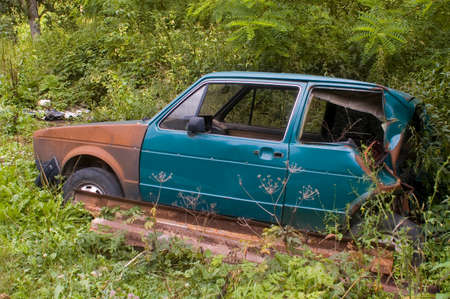 Abandoned old broken car in the green summer meadow photo