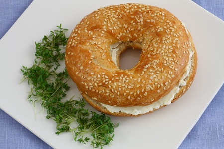 Bagel with cream cheese with watercress garnish photo