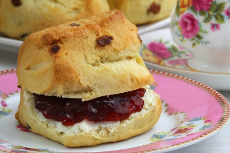 scone with strawberry jam and clotted cream, close up photo