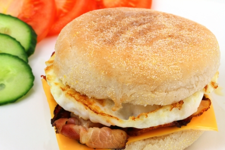 english cucumber: English muffin with fried egg, bacon, Cheddar cheese, tomato and cucumber Stock Photo