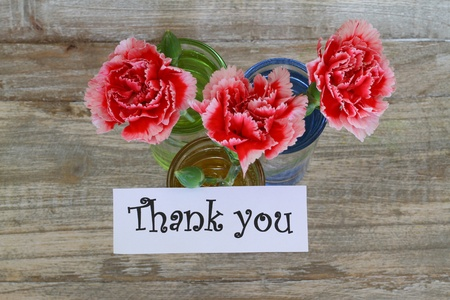 thank you note: Thank you note with red and white carnations on wooden background Stock Photo