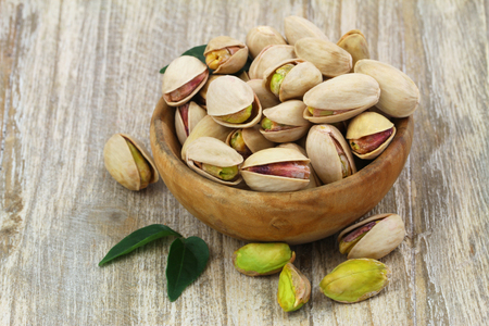 Pistachios with and without shell in wooden bowl with copy space photo