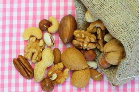 Selection of nuts in jute bag on pink checkered cloth photo