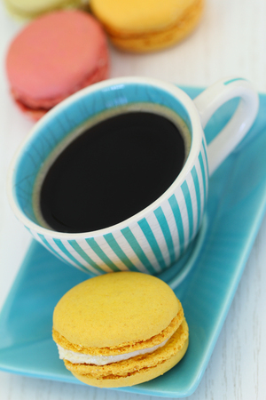 Lemon macaroon and cup of black coffee, close up photo