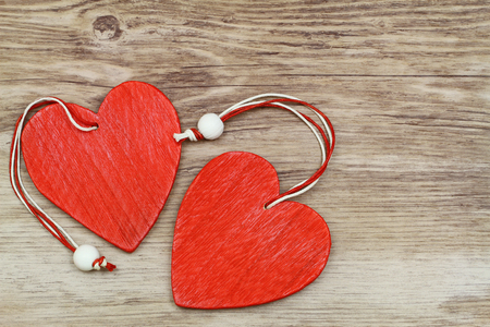 string together: Two red wooden hearts on wooden surface with copy space