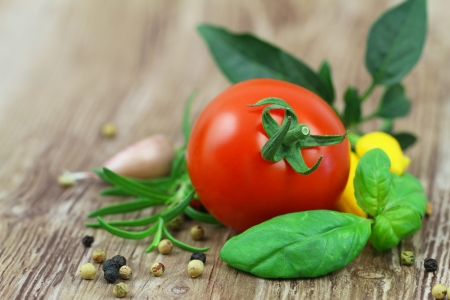 Fresh basil, tomato, rosemary, mixed peppers on wooden surface with copy space photo
