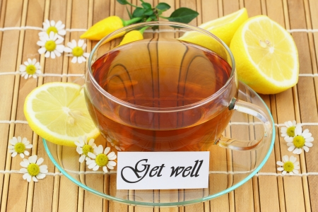 Get well card with cup of chamomile tea and lemon on bamboo mat photo