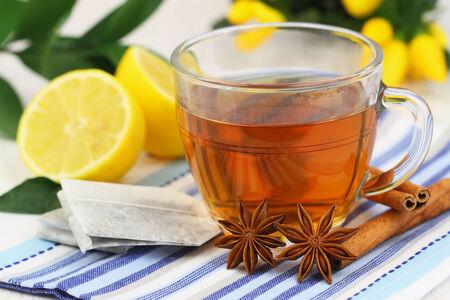 Tea, tea bags, fresh lemon, star anise and cinnamon sticks photo