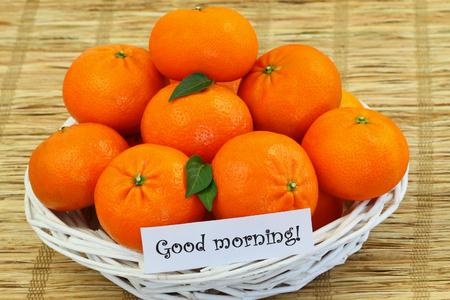 buena salud: Buena tarjeta de la ma�ana con la cesta de mimbre llena de mandarinas Foto de archivo