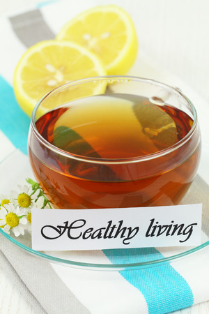 Healthy living card with cup of chamomile tea and lemon photo