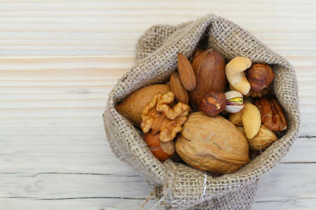 Selection of nuts in jute bag on wooden surface with copy space photo