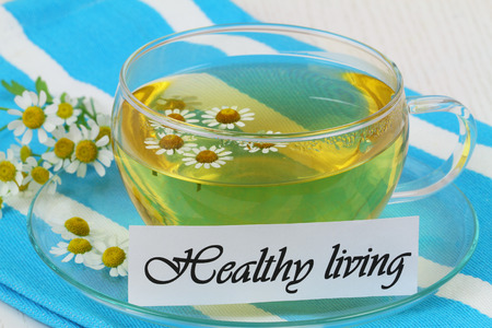 Healthy living card with cup of chamomile tea photo
