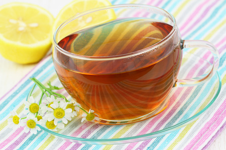Tea, fresh chamomile flowers and lemon photo