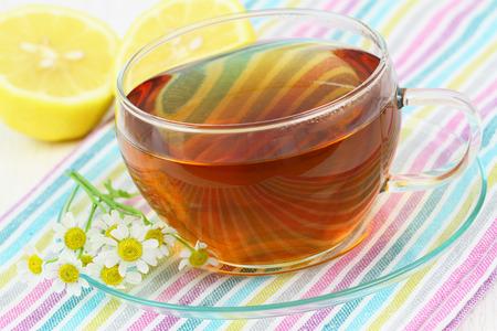 Tea, fresh chamomile flowers and lemon photo