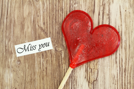miss you: Miss you card with heart shaped lollipop on wooden surface