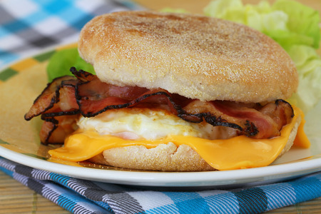 Muffin with fried egg, bacon and cheese photo
