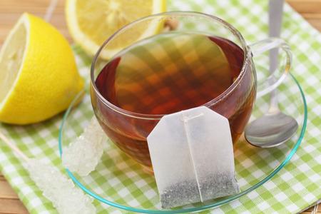 Tea bag leaning against cup of tea