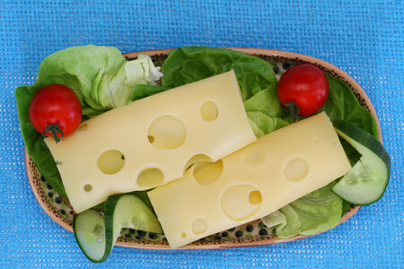 Swiss cheese on lettuce leaves with cherry tomatoes and cucumber