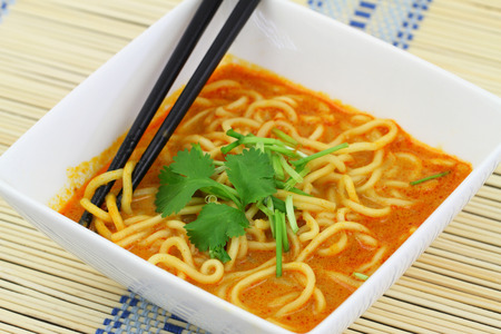 Hot curry noodles soup in bowl on bamboo mat photo