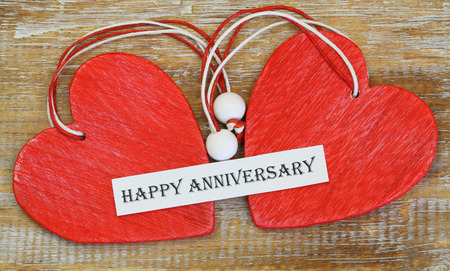 string together: Happy Anniversary card with two red wooden hearts Stock Photo