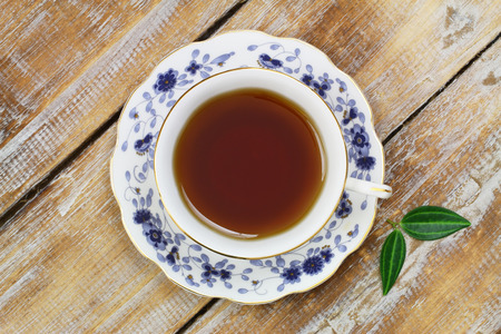 Tea in vintage cup on wooden surface photo
