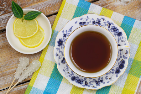 Tea in vintage cup and slices of lemon photo