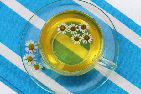 Cup of chamomile tea with fresh chamomile flowers photo