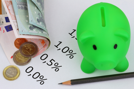 Piggy bank, interest rates and Euro banknotes and coins photo