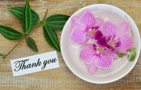 Thank you card with pink orchids on wooden surface
