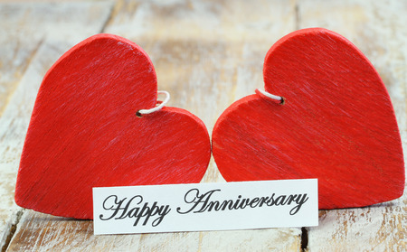 happy anniversary: Happy Anniversary card with two red wooden hearts Stock Photo