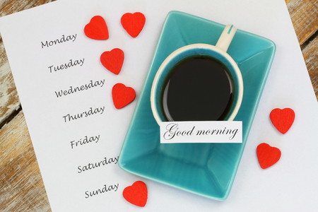 Good morning card with cup of tea and days of the week listed on white paper photo