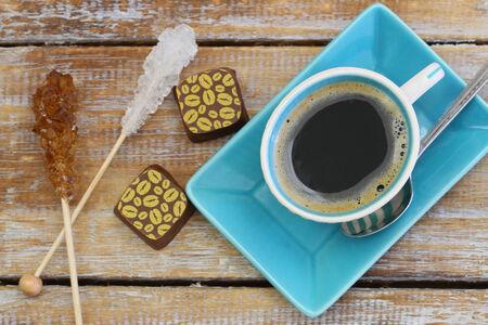 cafe bombon: Negro caf�, chocolates y palos de az�car en la superficie de madera r�stica