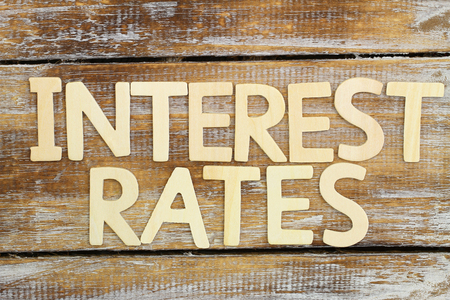 Interest rates written with wooden letters on rustic wooden surface Stock Photo