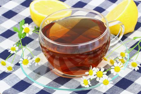 Tea with chamomile flowers and lemon photo