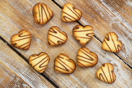 scattered in heart shaped: Heart shaped cookies scattered over rustic wooden surface