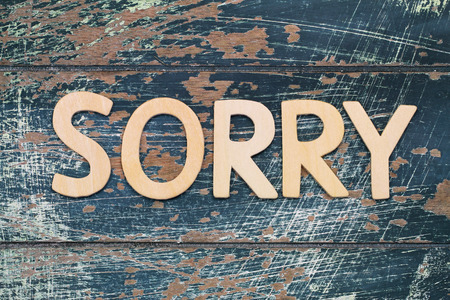 Sorry written with wooden letters on rustic blue surface