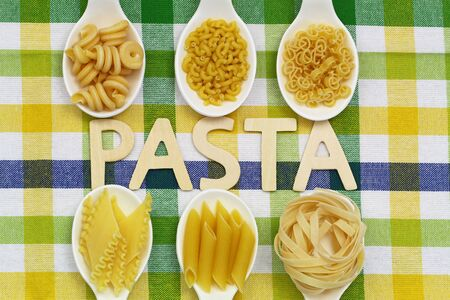 Pasta written with wooden letters on checkered cloth and uncooked pasta on porcelain spoons photo