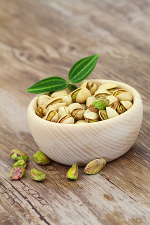 nutshells: Pistachio nuts in wooden bowl with copy space