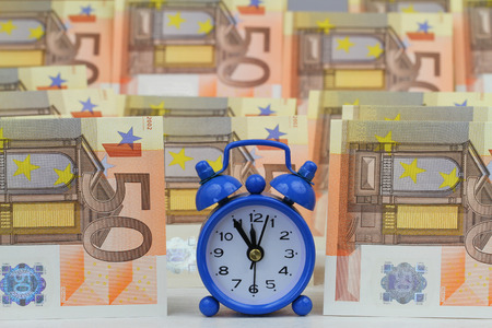 12 hour: Miniature clock with banknotes in the background Stock Photo