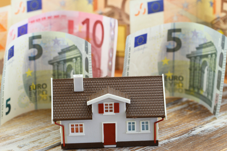 repayment: House with banknotes in the background Stock Photo