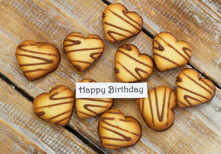 scattered in heart shaped: Happy birthday card with heart shaped cookies on rustic wood